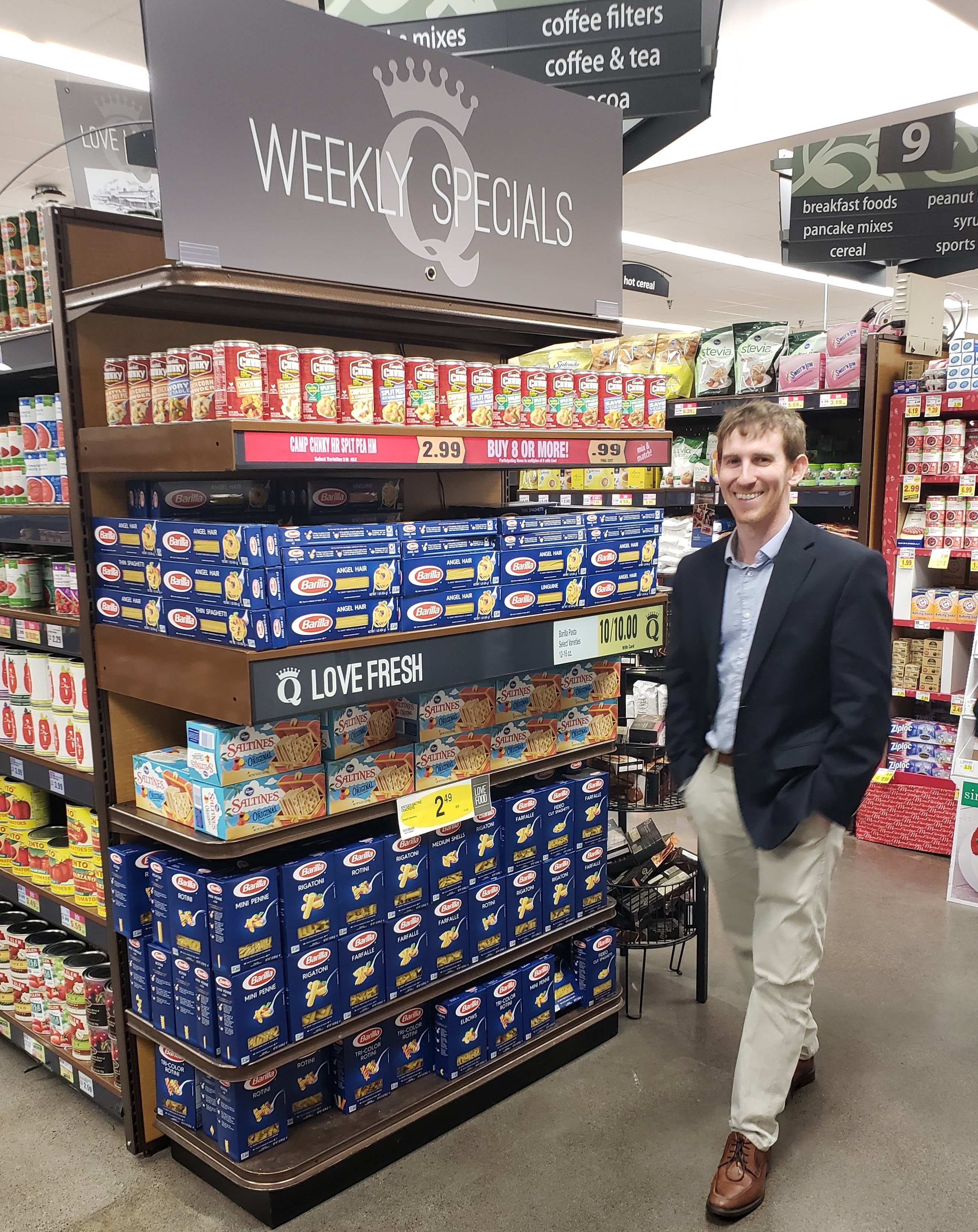 A Spur consultant next to his launched product at a grocery store.
